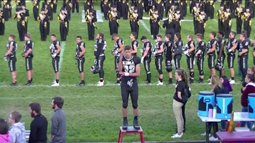 Kuna High football player signs the national anthem