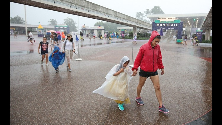 People leave Disney's Magic Kingdom theme park, in heavy rain, after it closed in Orlando, Florida in preparation for the landfall of Hurricane Matthew, on October 6, 2016. (Photo by GREGG NEWTON/AFP/Getty Images)